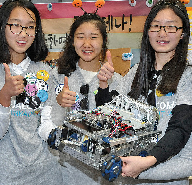"Qualcomm's Molly Gavin with FIRST Tech Challenge team ""Laonjena"" and their robot."
