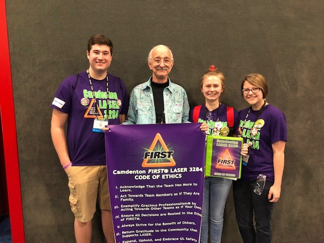"Students from LASER 3284 show the team's Code of Ethics to Dr. Woodie Flowers, FIRST Executive Advisory Board Co-Chair, Distinguished Advisor."" class="