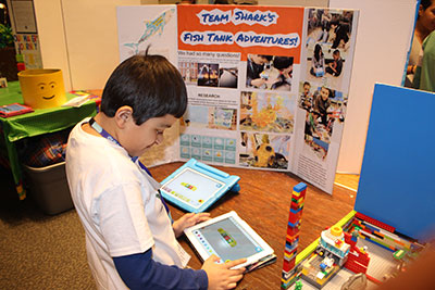 "A student from ""Team Shark"" uses an app to program the team's model."