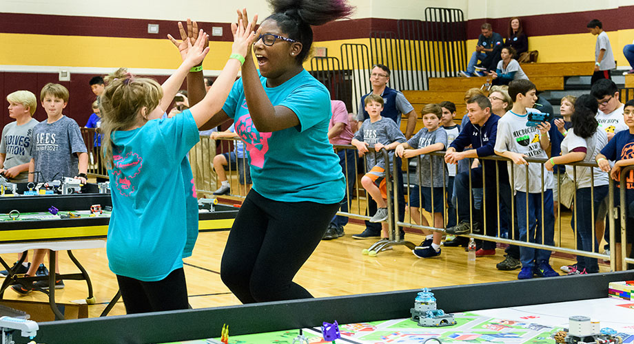 The Brainiac Maniacs celebrate during a FIRST LEGO League match.