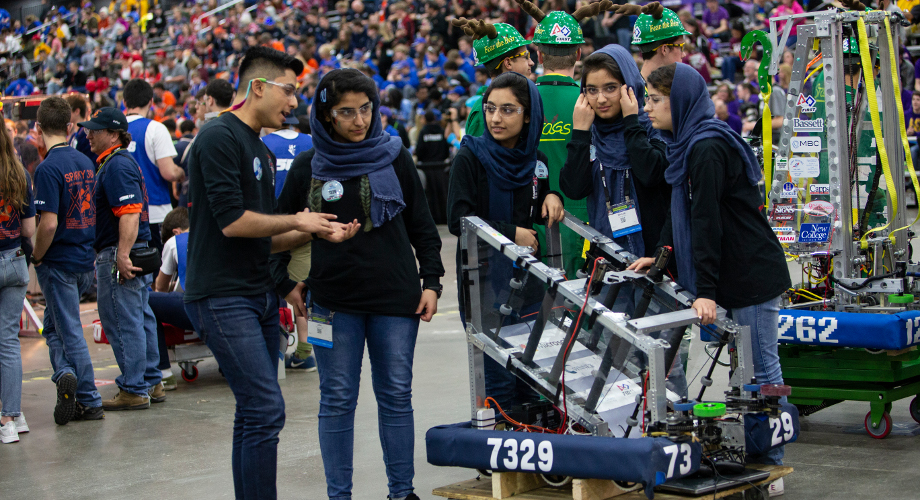"Students from FIRST Robotics Competition team ""The Afghan Dreamers"" prepare with their mentor before a match at the 2018 FIRST Championship in Detroit."