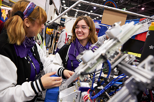 High school students work on their robot in the FIRST Robotics Competition pits at FIRST Championship.