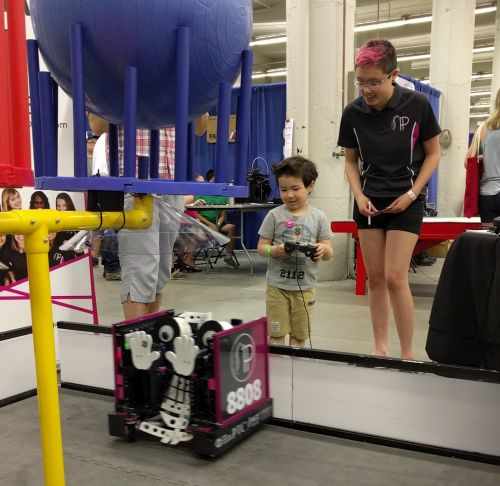 Rose encourages a young robot driver at a community outreach event.