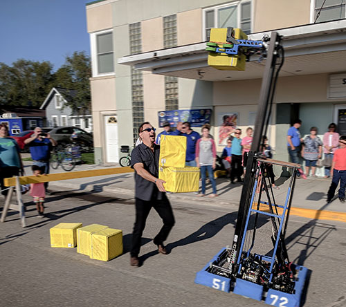 Director Joe Brandmeier stacks boxes with the team's robot.