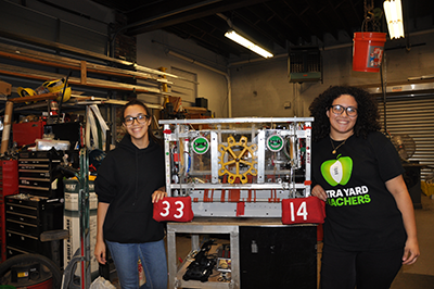 Sarai and Kim show the Mustang's 2017 robot during a tour of the team's build space.