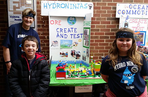 Students from a FIRST LEGO League Jr. team exhibit their Show Me poster and model at an expo in McLoud, Oklahoma.