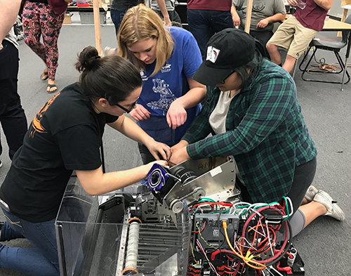 "Melanie works with her teammates on a robot for Team 987 ""High Rollers."""